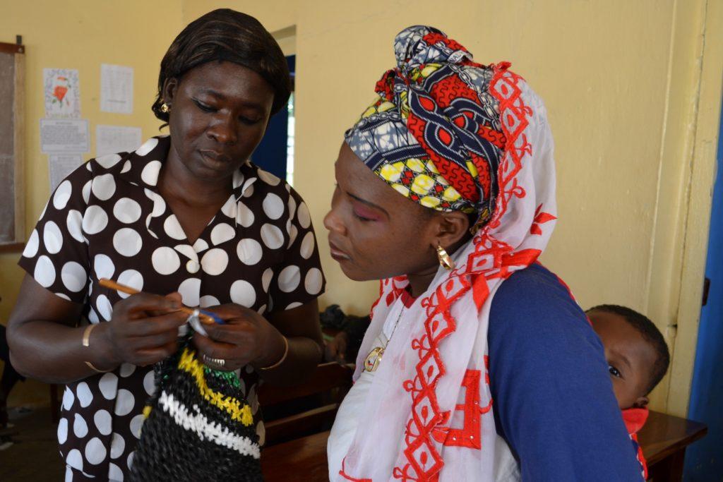 Odile Sannou, Workshopleiterin aus Benin, erklärt Baraka Oukpedjou aus Sokodé, wie sie den Henkel häkeln soll - Plastikmüll Plastikmüll Häkeln mit Plastikmüll in Togo (Christine Bertschi)