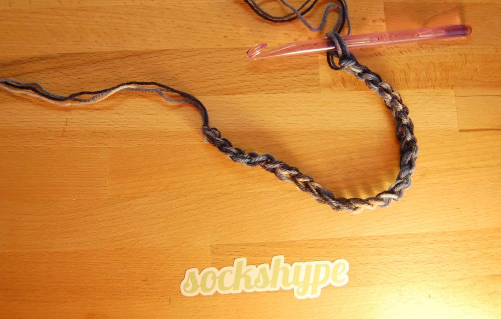Loop häkeln: Es werden 27 Maschen mit drei Fäden angeschlagen. Loop häkeln Anleitung: Loop häkeln im Korbmuster aus Wollresten