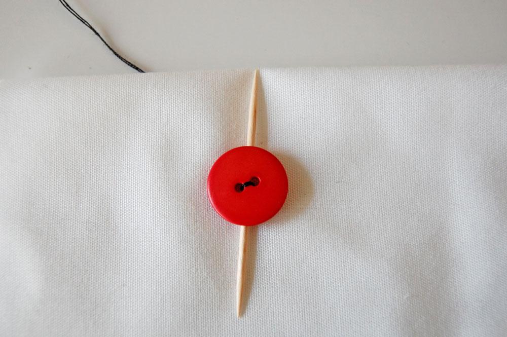 Knopf annähen - Zahnstocher zwischen Knopf und Stoff knopf annähen Zugeknöpft – Knopf annähen – So einfach geht es.