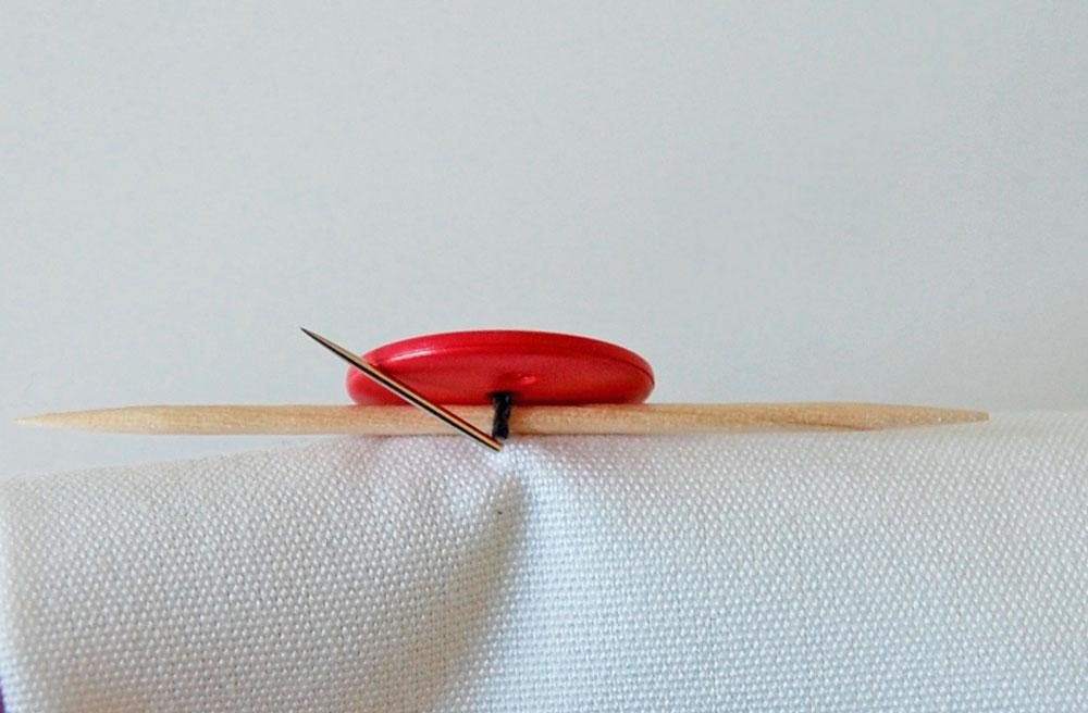 Knopf annähen - Nadel kommt zwischen Knopf und Stoff heraus knopf annähen Zugeknöpft – Knopf annähen – So einfach geht es.