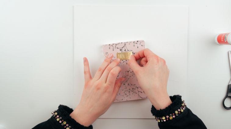 Beim Notizbuch gestalten klebt Marit ein gestaltetes Schild auf.