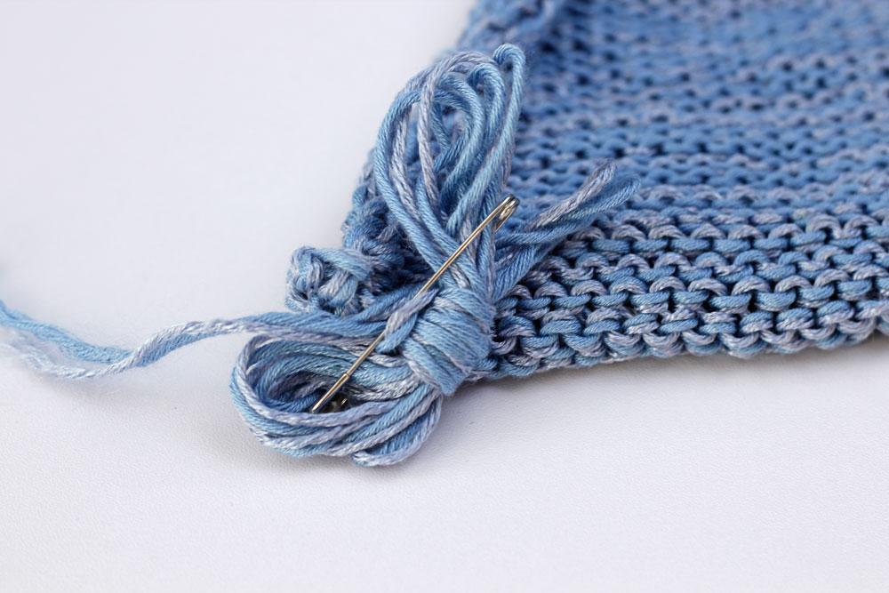 Strick-Tricks: Bleibt ein längeres Stück Faden bei der Maschenaufnahme übrig, so wird dieser aufgewickelt und mit einer Sicherheitsnadel am Strickstück befestigt.