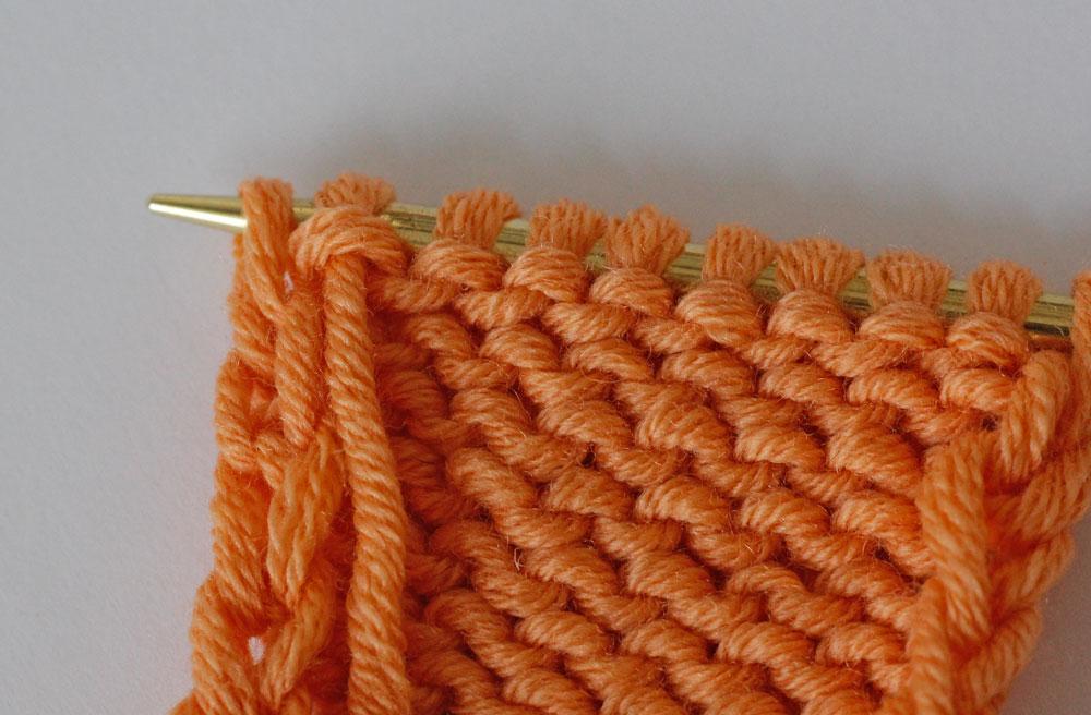 Randmaschen stricken: Bei der Kettmasche wird die letzte Masche einer Reihe wie zum Linksstricken abgehoben.