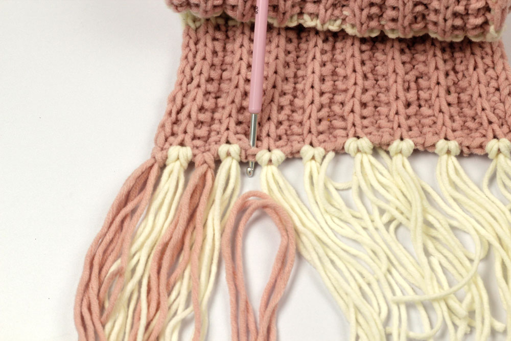 Schal stricken - Mit der Häkelnadel stichst du von vorne nach hinten in die Masche ein, um dann das auf die Hälfte geknickte Fransenbüschel einzuknüpfen.