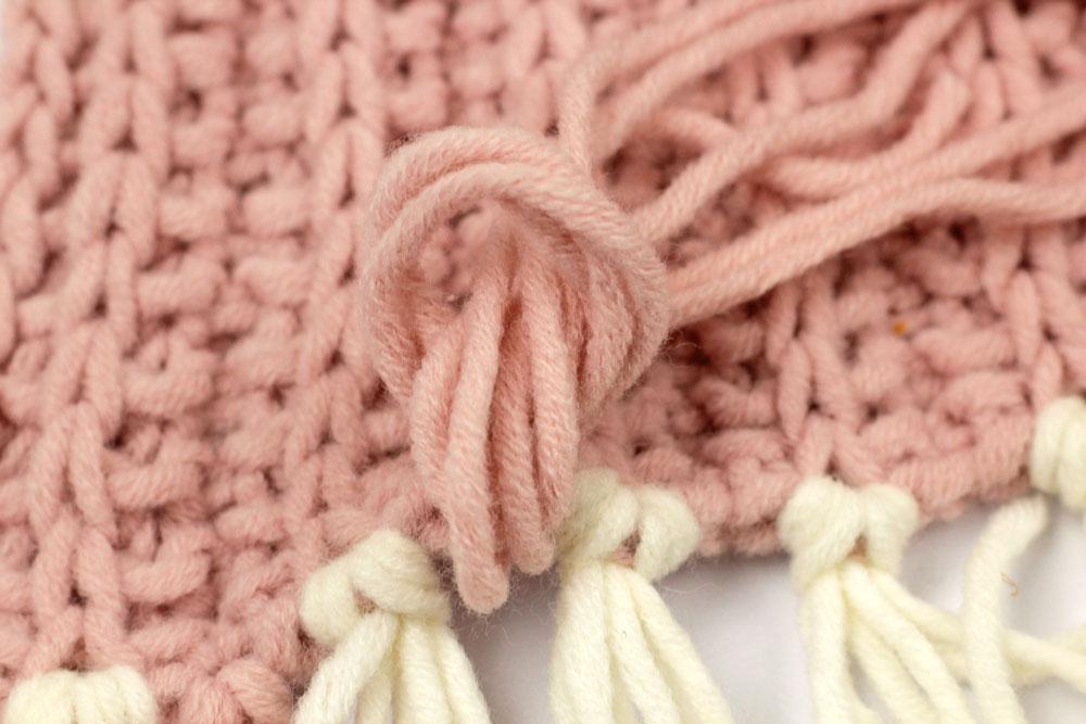 Schal stricken - Die Fadenenden werden durch die Schlinge gezogen und fest gezurrt.