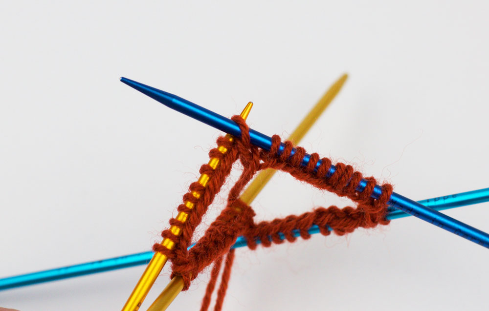 Runde schließen - Überzug: Die überzogene Masche wird auf die erste Nadel (gelb) geschoben.