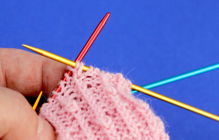 BeritSocks - Das Knötchen: Es wird eine zweite Masche – eine rechtsverschränkte Ma-sche gestrickt. Die ursprüngliche Masche bleibt noch auf der linken Nadel.