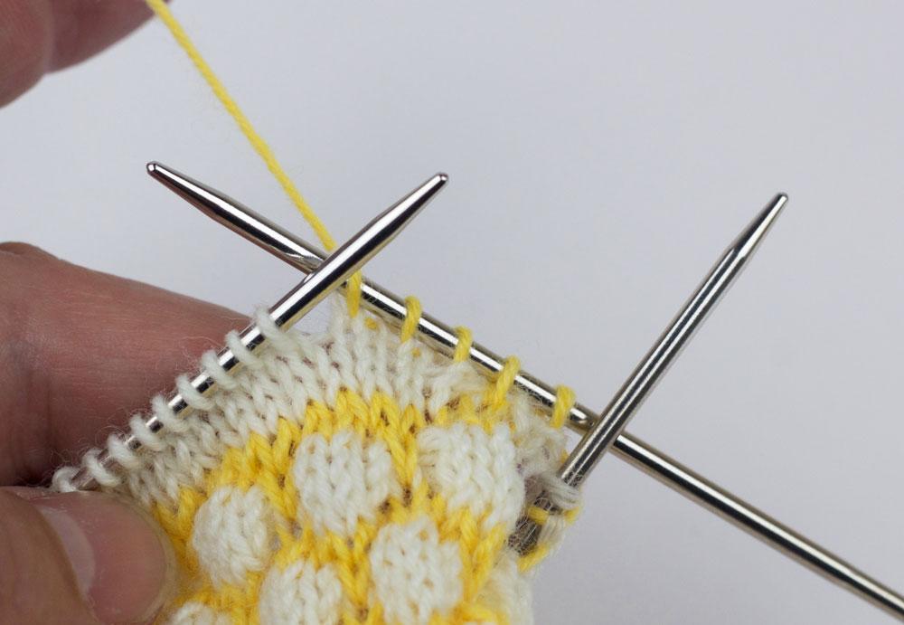 Eine nachträglich eingestrickte Ferse für die CajaSocks - - Es werden zunächst drei rechte Maschen in Gelb (Farbe 2) gestrickt.