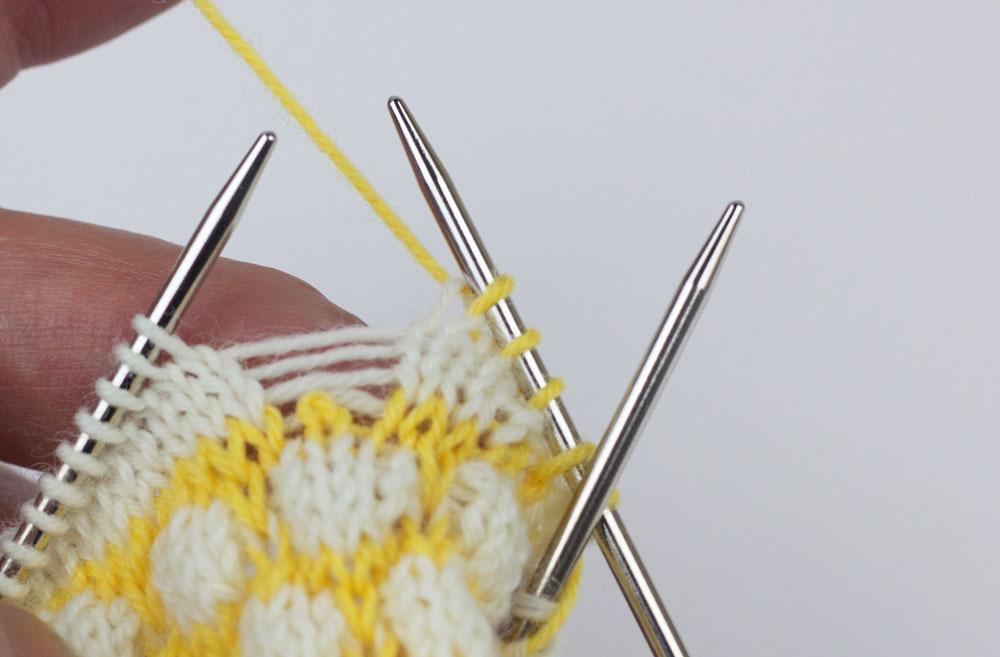 Eine nachträglich eingestrickte Ferse für die CajaSocks - Du hast für jede der vier aufgelösten Maschen einen Querfaden sichtbar. Die erste gelbe Masche (in Farbe 2) wird nicht fallen gelassen.