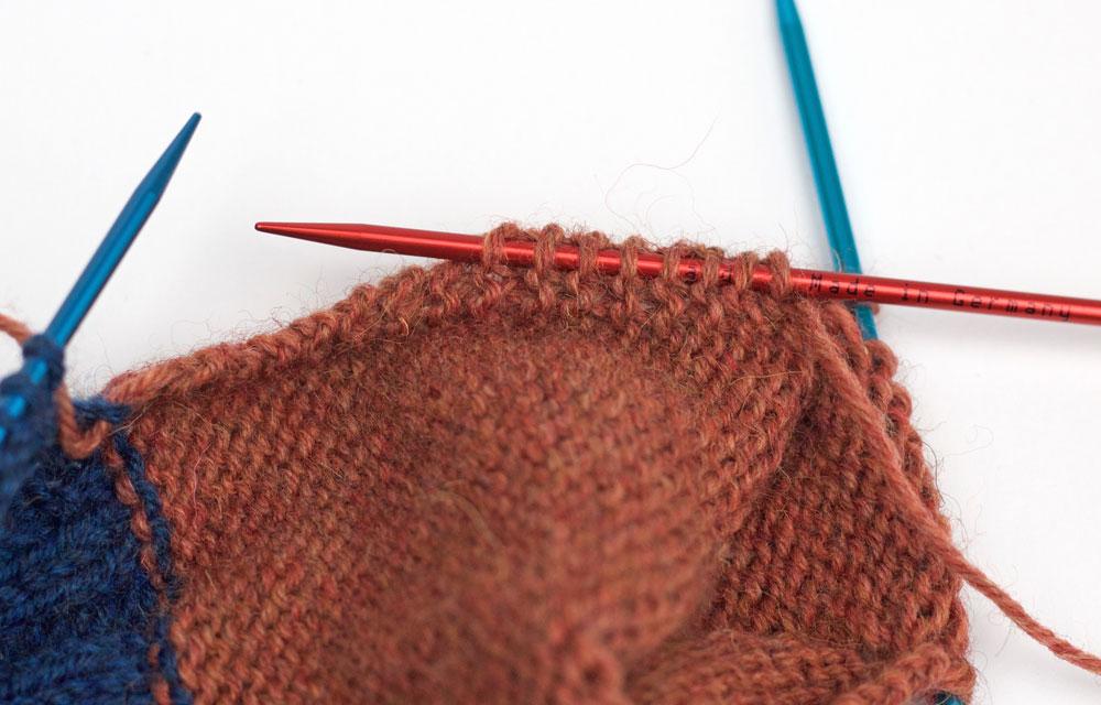 ElisSocks - Eine freie Nadel wird in die Knötchen der Fersenwand geschoben.