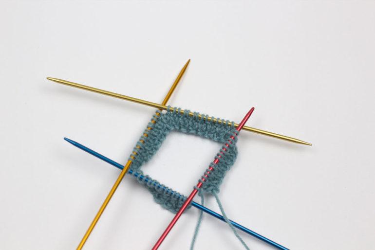 Strümpfe stricken: Die Nadeln werden zur Runde geschlossen.