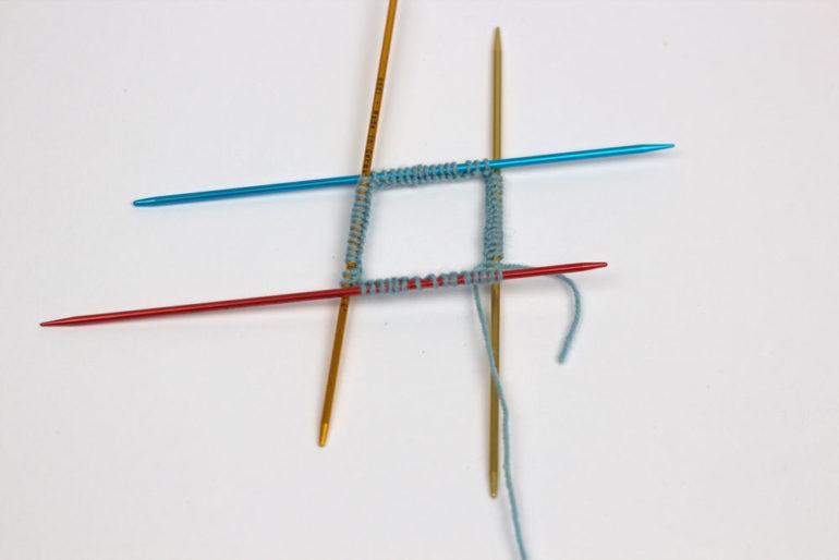 Strümpfe stricken: Ordne die Nadeln zur Runde. Achte darauf, dass sich die Nadeln nicht verdrehen.