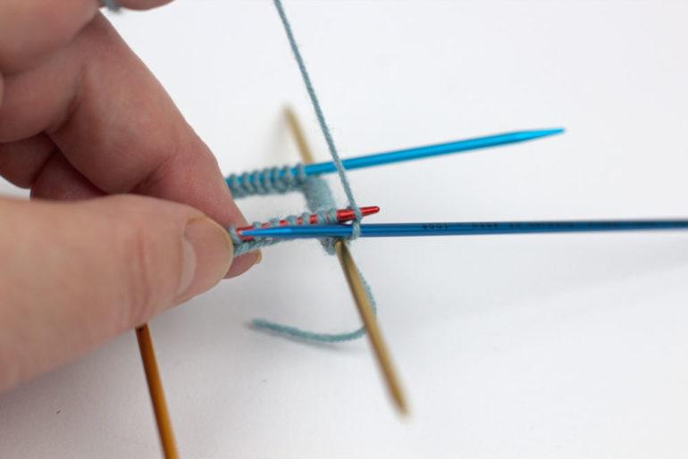 Strümpfe stricken: Mit der 5. Nadel werden jetzt die Maschen der ersten Nadel im Bündchenmuster abgestrickt.
