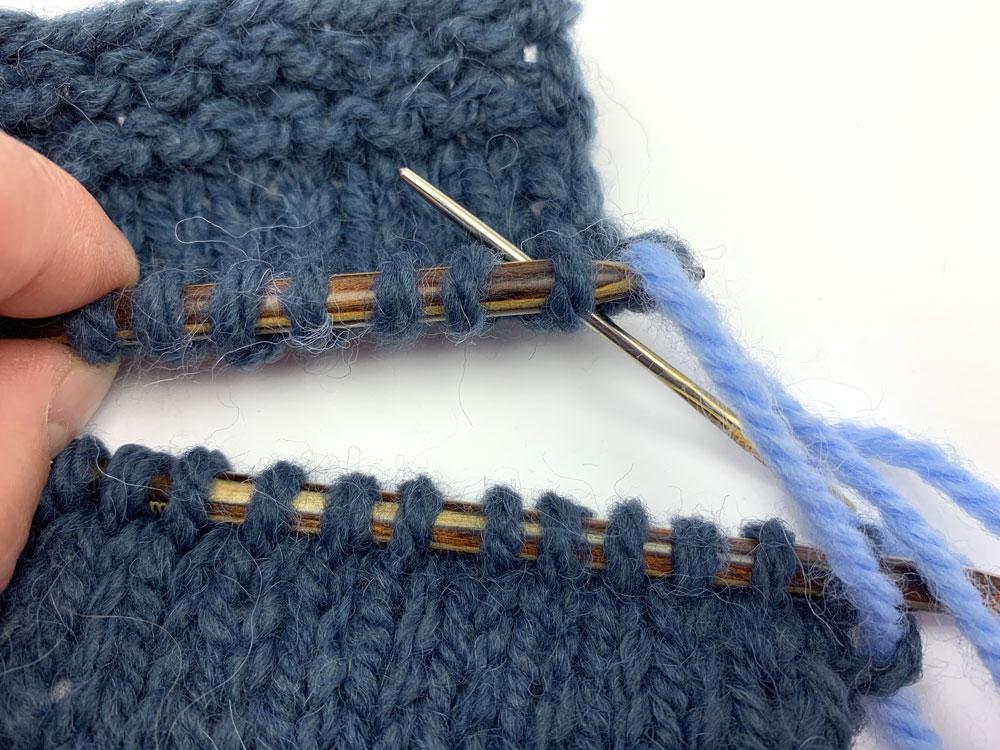 Schritt 3: Die Masche wird durch die zweite Masche auf der oberen Nadel von unten geschoben.