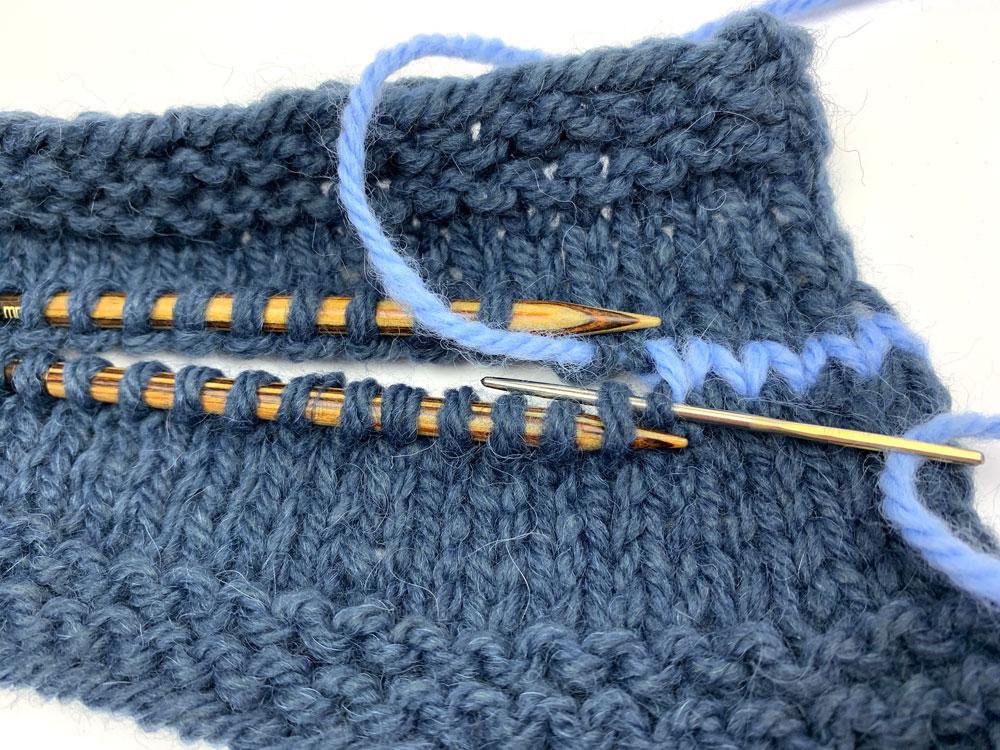 Schritt 6: Auf der unteren Stricknadel schiebst du die Nadel an der Ausstichstelle des Fadens von vorne in die Masche neben der Nadelspitze und gleich im Anschlussvon hinten durch die Masche auf der Stricknadel.