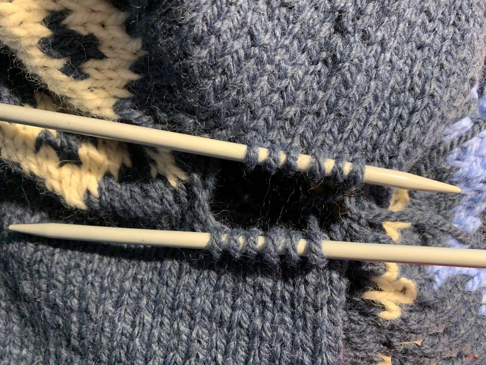 Die auf Sicherheitsnadeln geparkten Maschen für den Armsteg werden auf jeweils zwei Stricknadeln pro Ärmel verteilt. Dabei befinden sich die Maschen vom Körper auf einer Nadel. Die vom Ärmel auf der anderen Nadel.