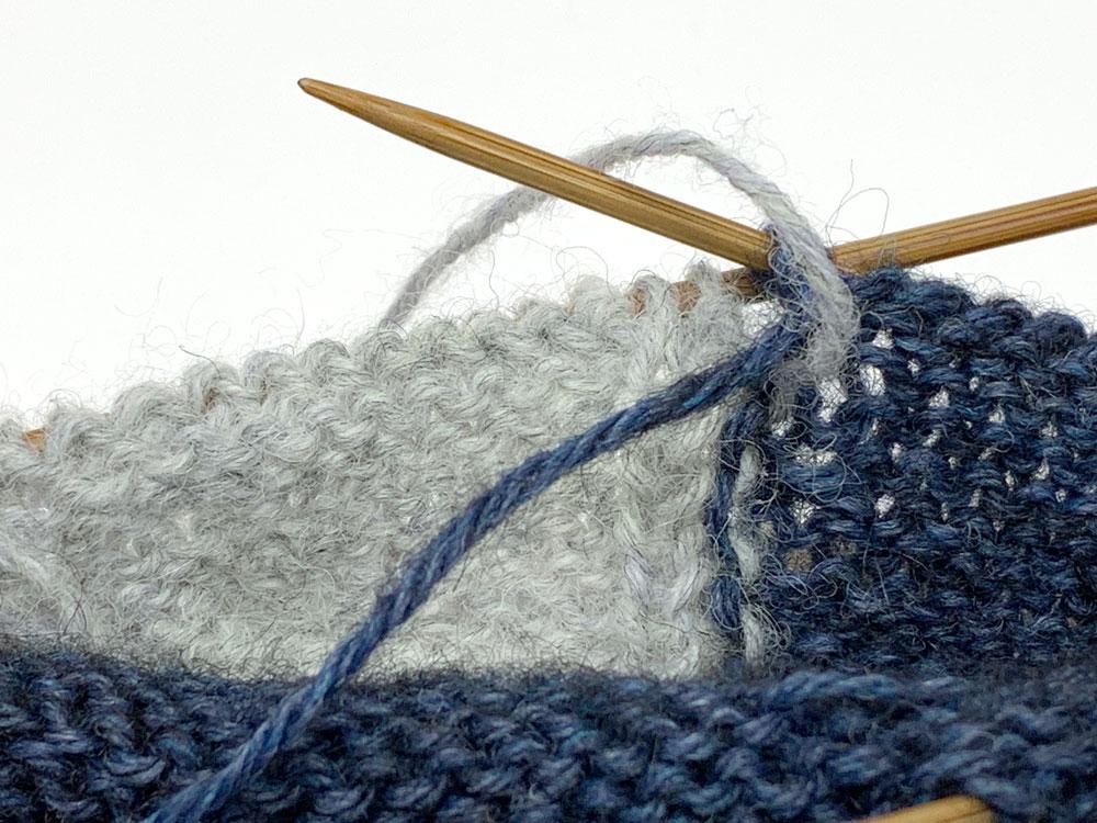 Verkreuzen der Fäden in der Rückreihe. Der Faden der Hauptfarbe (blau) wird in der Rückreihe nach links geführt. Der Faden der Nebenfarbe (grau) kommt von vorne. Es folgt eine linke Masche mit der Nebenfarbe.