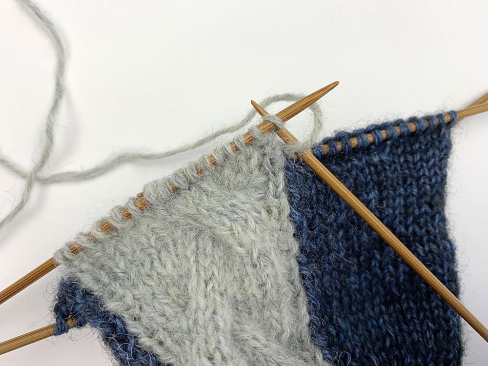 Zu Beginn der Hinreihe wird ein Umschlag gemacht. Dann wird die folgende Masche rechtsverschränkt gestrickt, da sie sich durch das Zusammenstricken zuvor verdreht auf der Nadel befindet.