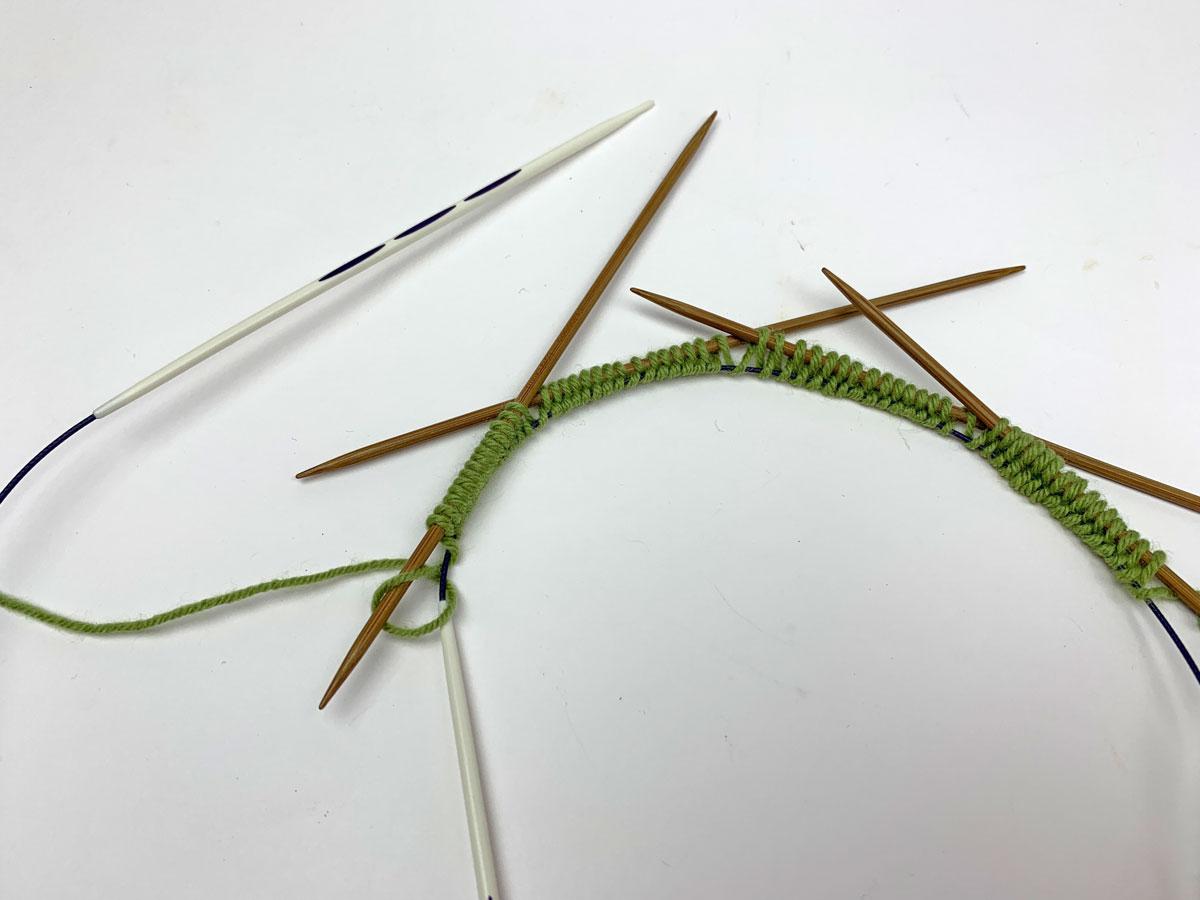 Die provisorischen Maschen werden bereits auf vier Nadeln des Nadelspiels verteilt. Das Seil der Rundstricknadel führt die provisorischen Maschen.