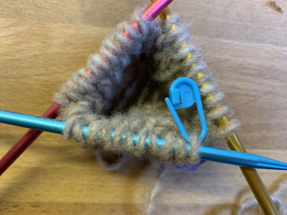 Ein weiterer Maschenmarkierer wird durch die erste linke Masche auf der Nadel gezogen und nach hinten geschoben.