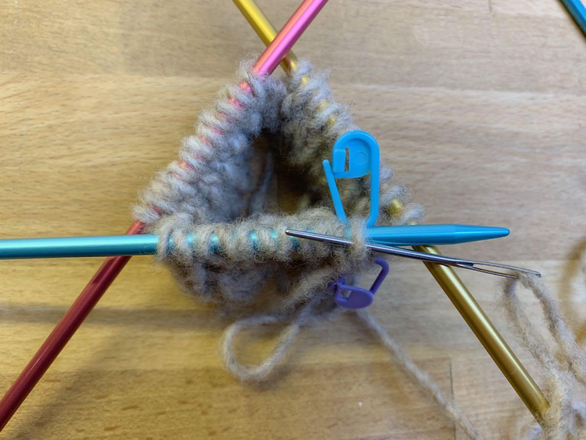 Die Nadel wird wie zum Linksstricken durch die erste linke Masche geschoben.