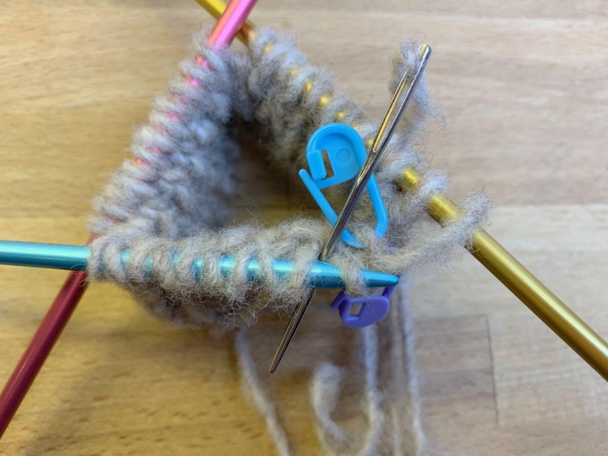 Die Nadel wird von hinten nach vorne zwischen linker und rechter Masche hindurchgeschoben.
