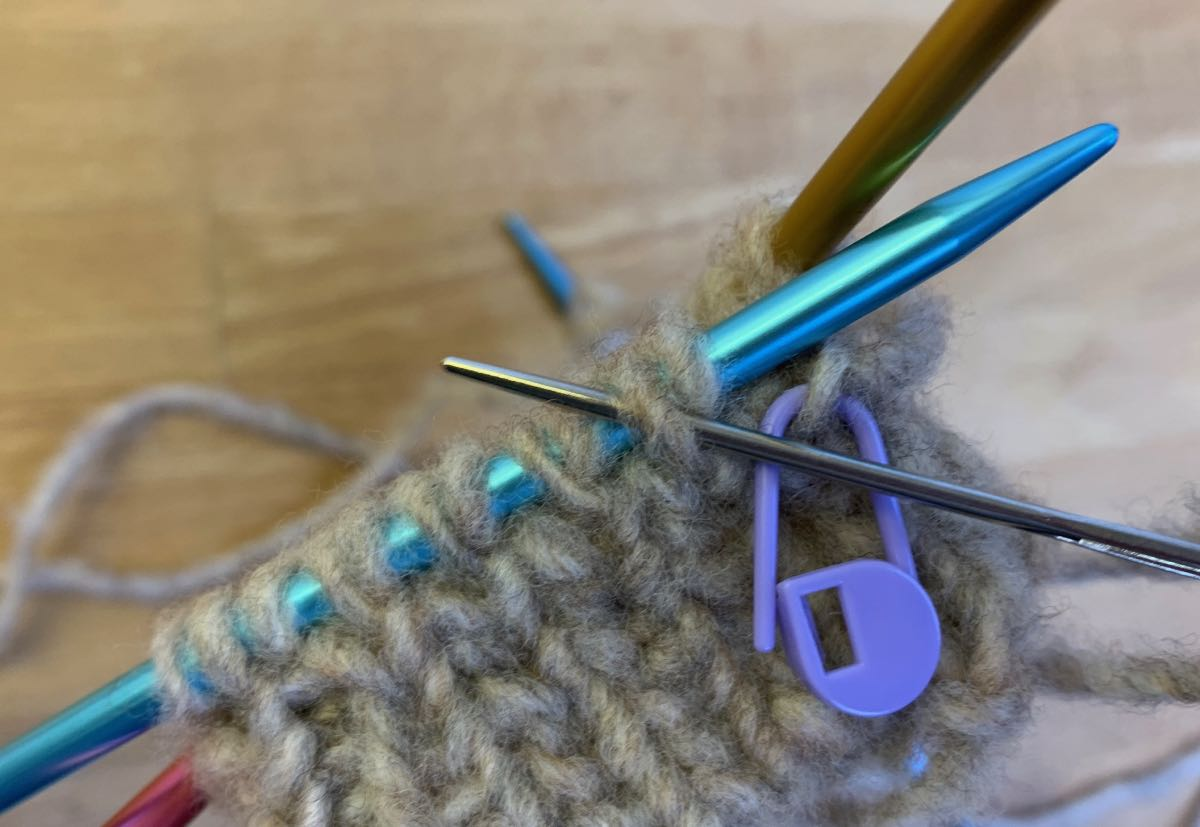 Italienisches Abketten: Nadel wird wie zum Linksstricken durch die erste rechte Masche auf der Nadel geschoben.