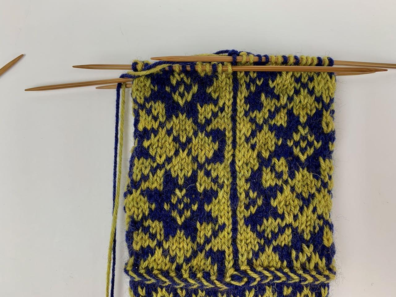 Auf der Beininnenseite wird das Muster mittels einer Linie aus drei Maschen (hier: gelb blau gelb) unterbrochen.