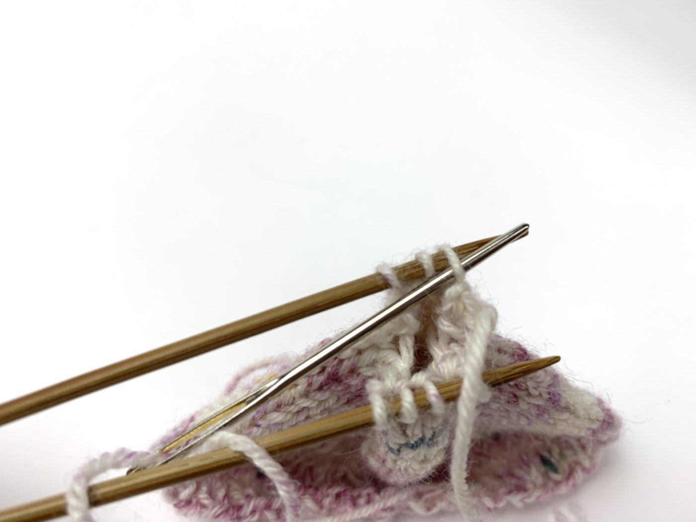 Wie zum Rechtsstricken wird die Nähnadel durch die rechte Masche auf der hinteren Nadel geschoben. Die Masche bleibt auf der Nadel.