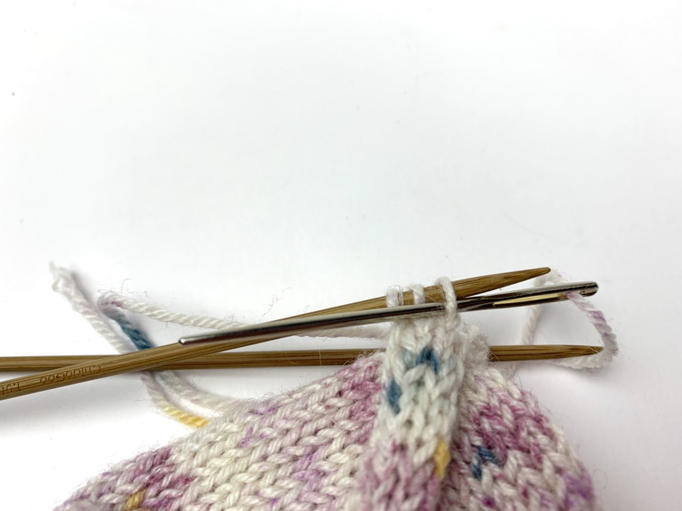 Die Nähnadel wird wie zum Linksstricken durch die Masche geschoben. Masche verbleibt auf der Nadel.