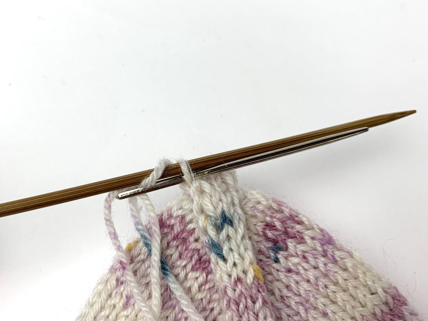 Schiebe die Nähnadel wie zum Rechtsstricken durch die letzte Masche auf der vorderen Nadel und lasse sie von der Stricknadel gleiten.