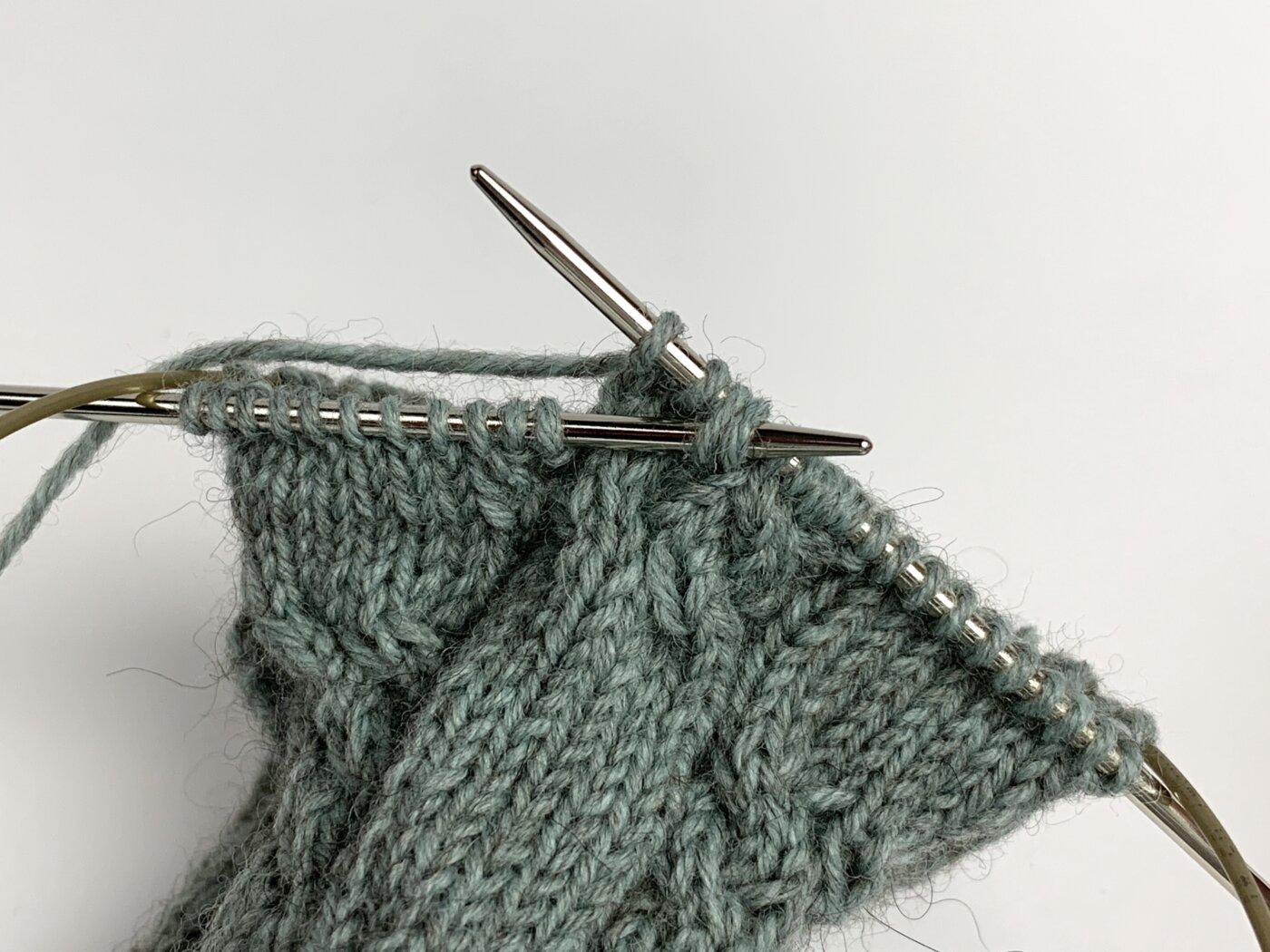 Die abgehobenen Maschen werden auf die linke Nadelspitze geschoben.