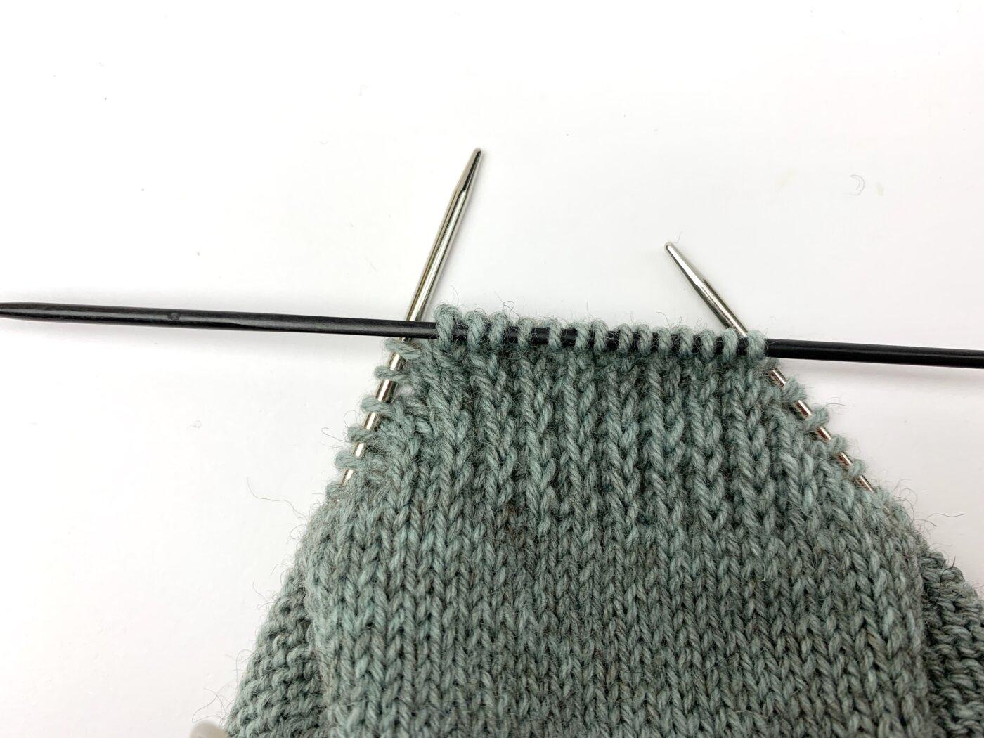 Zur Verdeutlichung habe ich die Maschen zwischen den abgehobenen Maschen auf eine separate Nadel geschoben.