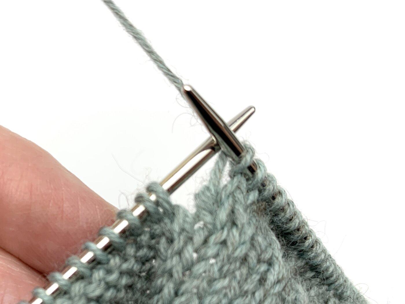 Toe Up Socken stricken - In der Hinreihe werden die Maschen bis eine Masche vor der Lücke rechts gestrickt. Die folgende Masche wird abgehoben, die nächste Masche wird rechts gestrickt, die abgehobene Masche über die soeben gestrickte gezogen.