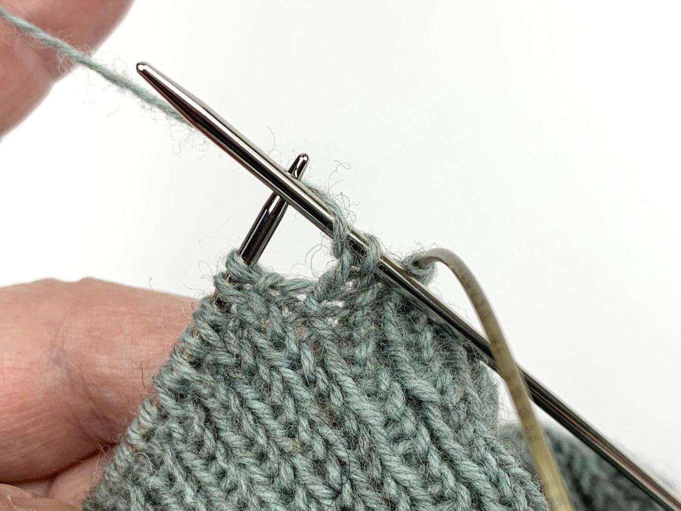 Für den Umschlag vor einer linken Masche ziehst du den Faden von vorne nach hinten über die rechte Nadel.