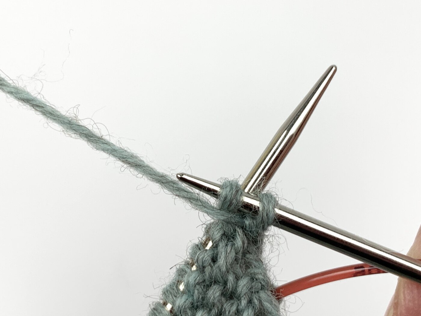 Schiebe die rechte Nadelspitze von rechts nach links vor der linken Nadel durch den Querfaden und stricke ihn links ab. Der Querfaden wird hierbei verdreht. Dadurch entsteht hier kein Loch.