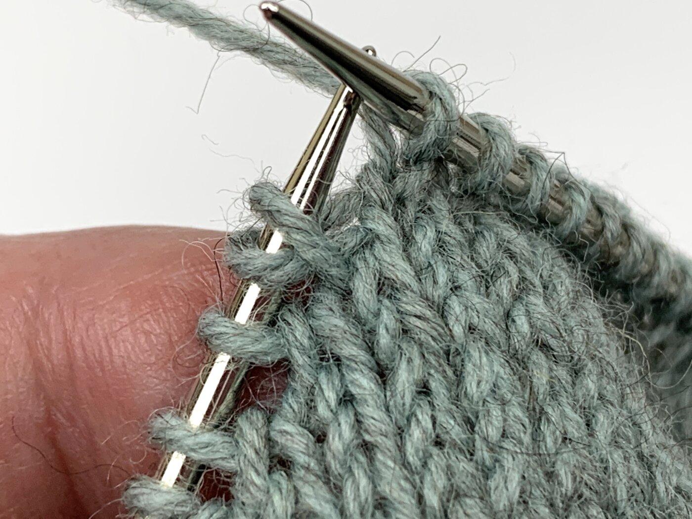Das rechte Beinchen der Muttermasche wurde auf die linke Nadel gehoben.