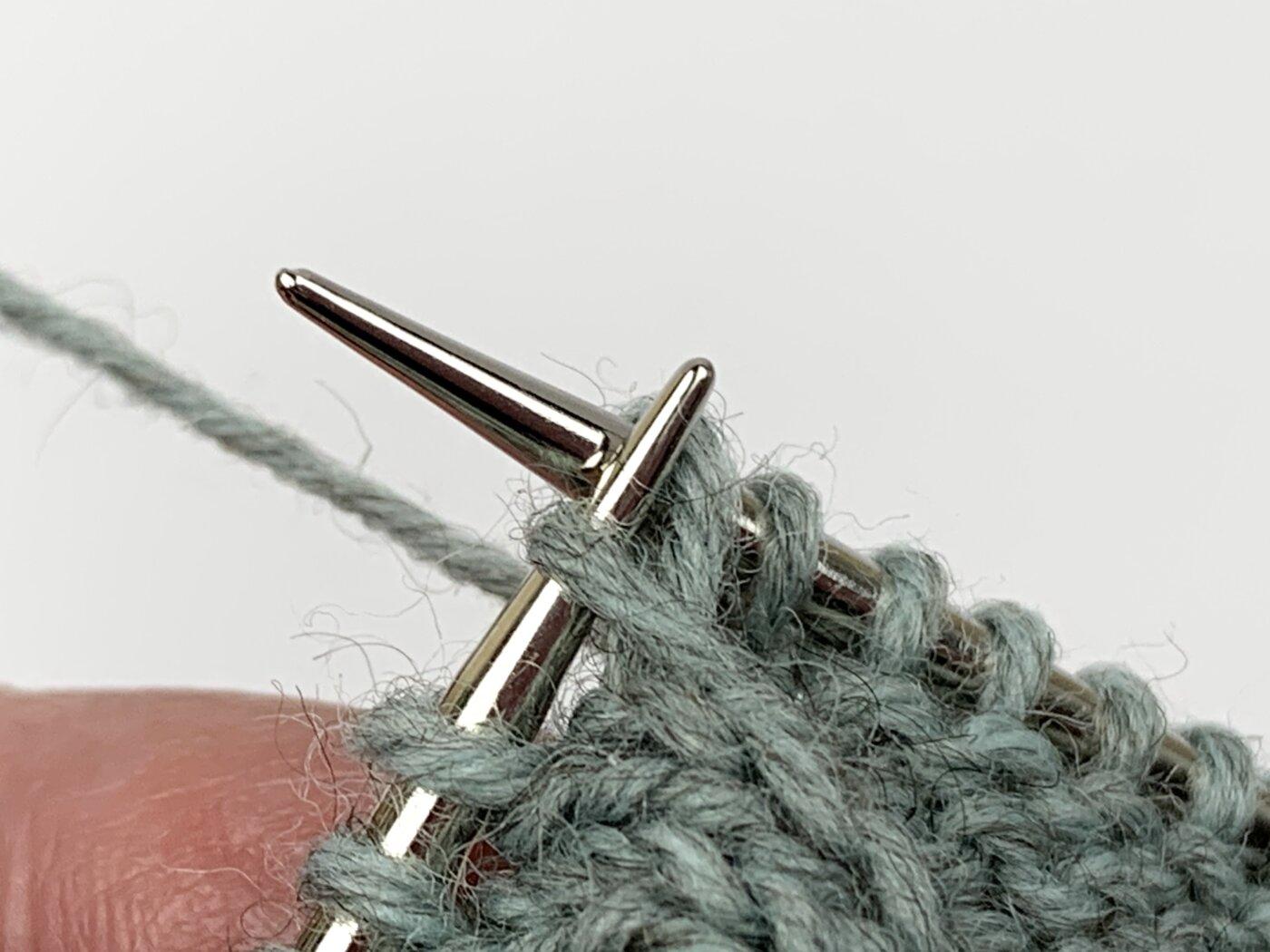 Das linke Beinchen der Muttermasche wird mit der linken Nadel auf die rechte Nadelspitze gehoben.