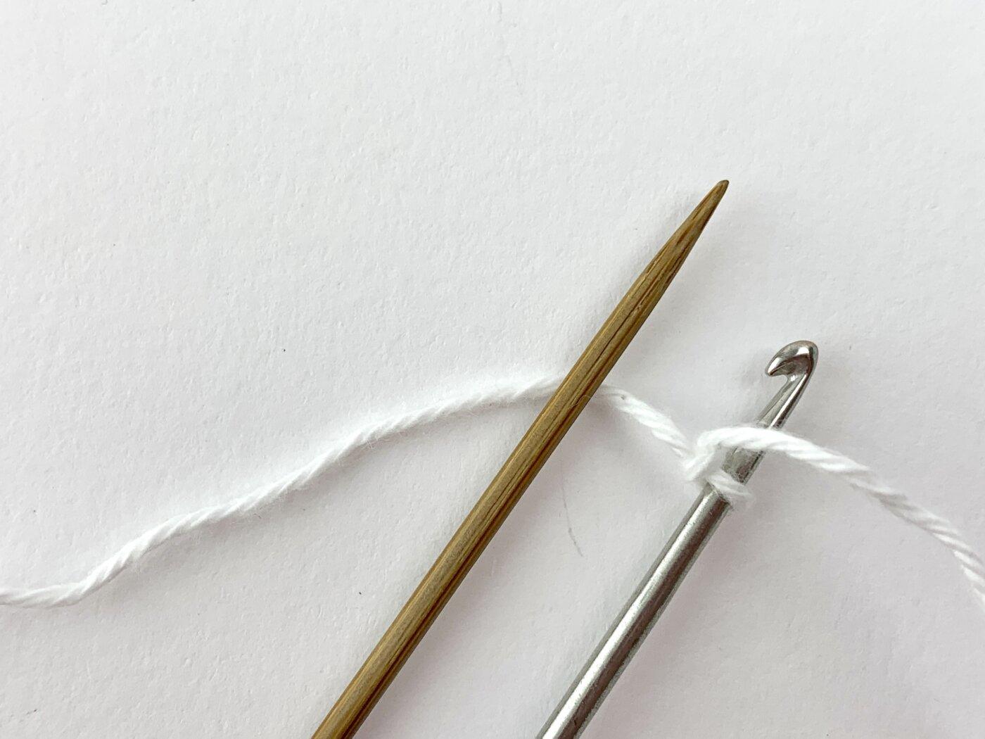 Der Arbeitsfaden hinter der Stricknadel des Nadelspiels