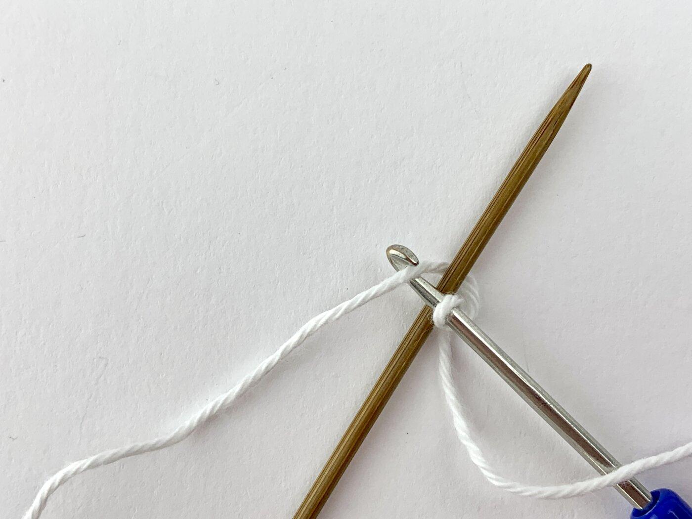 Mausezähnchen stricken - Der Arbeitsfaden wird von vorne mit der Häkelnadel gegriffen und durch die Schlinge auf der Häkelnadel gezogen.
