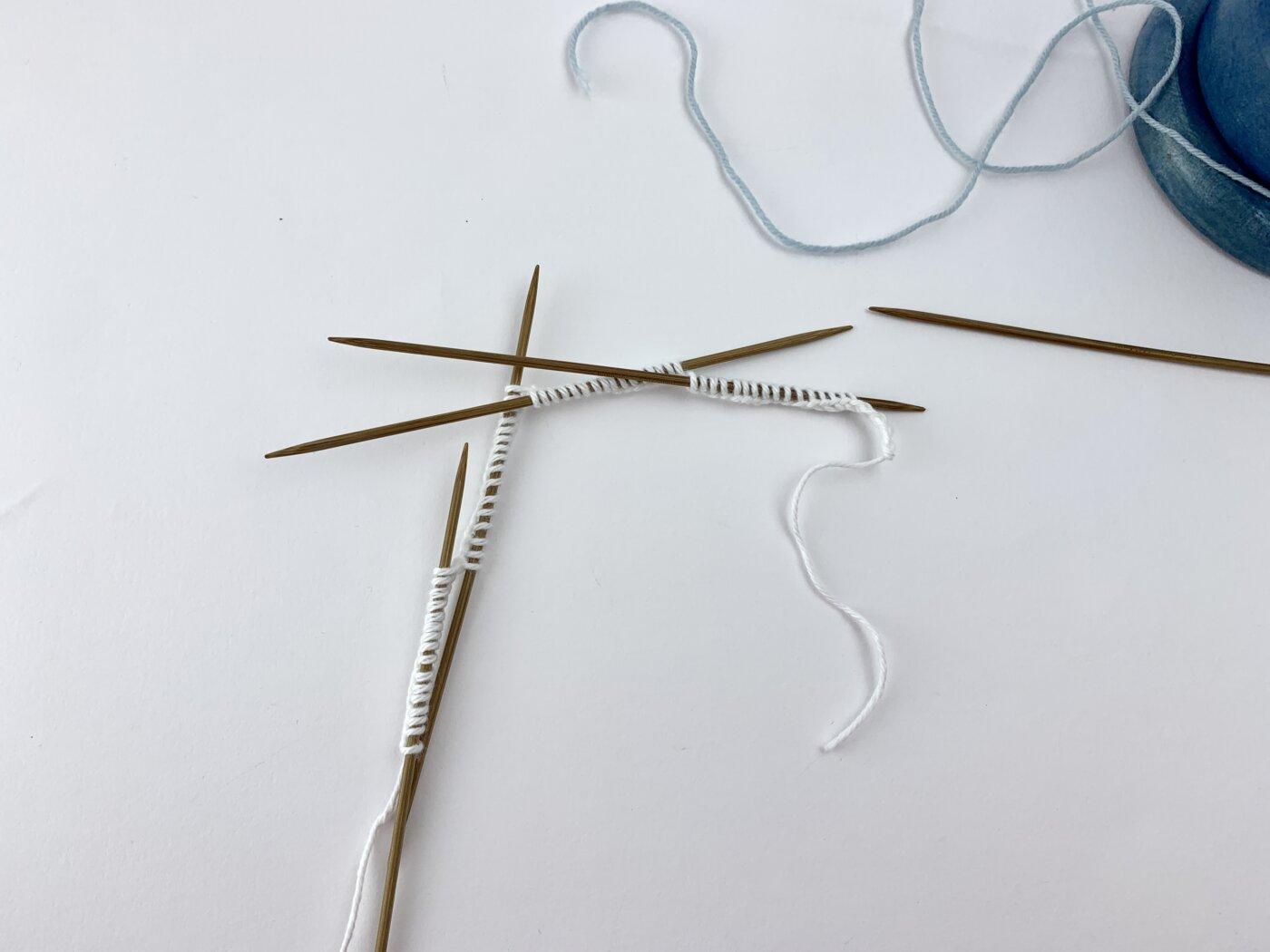 Beim Stricken in der Runde können die Maschen auf vier Nadeln verteilt werden.